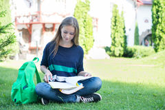 School or college girl sitting with book and bag studying in a park Stock Images