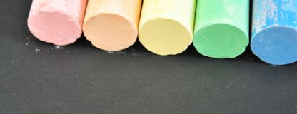 School colored crayons on a dark background close-up. Study and education are conceptual. Color chalk stock photography