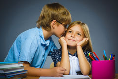 School Communication concept. boy whispering in ear of girl. Boy whispering in the ear of Teenager or girl on gray background. Communication concept Stock Photography