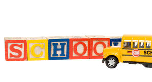 School Concept. With baby blocks spelling the word school and a yellow school bus Stock Image