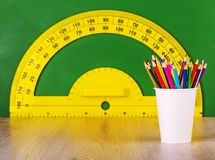 School concept colore penciil and yellow protractor on green chalkboard. School concept colore penciil and yellow protractor on green chalkboard stock photography