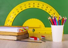 School concept: colore pencil, book, ruler, scissors and green chalkboard with yellow protractor. School concept: colore pencil, book, ruler, scissors and green royalty free stock photo