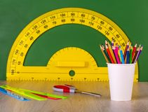 School concept colore pencil, ruler, scissors and yellow protractor. On green chalkboard stock photo