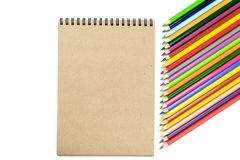 School Concept. Colored pencils, notebooks on brown and beige background. Design concept - Top view of notebook. And color pencil collection isolated on white royalty free stock images