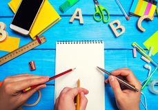 School concept, teamwork. Three hands with pencils and pens point to a notebook with white pages on the desktop blue wood stock photography
