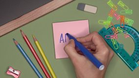 School concept. Womans hand writing APRIL on notepad. School supplies and stationery on the desk stock footage