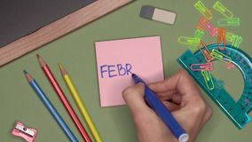 School concept. Womans hand writing FEBRUARY on notepad. School supplies and stationery on the desk stock footage