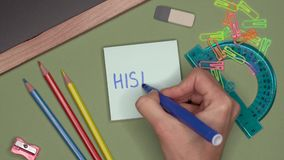 School concept. Womans hand writing HISTORY on notepad. School supplies and stationery on the desk stock video