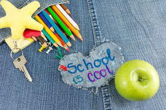 School is cool sign with creative learning objects. On blue jeans Stock Images