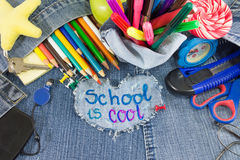 School is cool sign with creative learning objects. On blue jeans Stock Photography