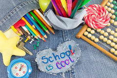 School is cool sign with creative learning objects. On blue jeans Royalty Free Stock Photo