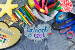 School is cool sign with creative learning objects. On blue jeans Stock Photo