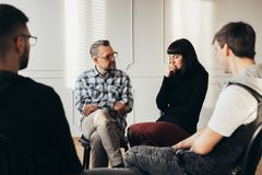 School counselor talking to depressed teenager during group therapy stock photography