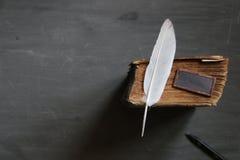 School courses idea. Feather pen and old book on blackboard. Vintage composition. School courses idea Stock Image