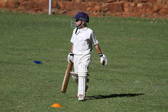 School cricket boy bat in hand. A young school cricket sport boy is walking with a cricket bat and ball in his hand. He is focused on the task ahead Stock Photos