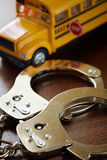 School criminality. Criminal concept with handcuffs and school bus, selective focus on nearest part royalty free stock photo