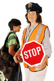 School Crossing Guard. A mature woman school crossing guard holding out her stop sign as a student passes behind her.  Isolated Royalty Free Stock Photography