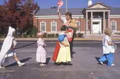 School crossing guard helping children. In Halloween costumes, Webster Groves, Missouri Royalty Free Stock Images