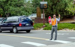 School crossing guard keeps kids safe. September 2017 Denver CO USA; a man directs traffic outside a grade school to help keep kids safe while crossing the Stock Photo