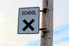 School Crossing Sign on a Power Pole with Cloudy Sky Background Royalty Free Stock Photos