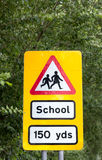 School Crossing Sign. A yellow school crossing sign among trees Stock Photography