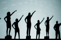School Dance. A silhouette of elementary children dancing during a school program. The children are back-lit and behind a white screen Stock Photography