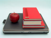 School day. Laptop with stack of books, red apple and red pencils on blue background Stock Photos