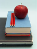 School day. Laptop with stack of books, red apple and red pencils on blue background Royalty Free Stock Image