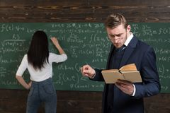 School day. Teacher man in glasses read problem statement from textbook to girl student. Learning math enables me to stock photos