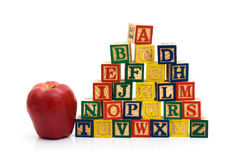 School Days. A stack to color wooden blocks of the alphabet with an apple over white, Schools Days Royalty Free Stock Images