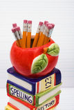 School Days. A stack of books with an apple sitting on top on a loose leaf background, School days stock photo