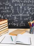 School desk in classroom, with books on background of chalk board with written formulas. Soncept Teacher`s Day. School desk in the classroom, with books on stock photos