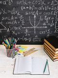 School desk in classroom, with books on background of chalk board with written formulas. Soncept Teacher`s Day. School desk in the classroom, with books on royalty free stock photography