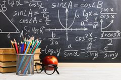 School desk in classroom, with books on background of chalk board with written formulas. Soncept Teacher`s Day. School desk in the classroom, with books on royalty free stock images