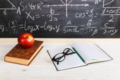 School desk in classroom, with books on background of chalk board with written formulas. Soncept Teacher`s Day. School desk in the classroom, with books on stock images