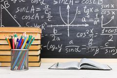 School desk in classroom, with books on background of chalk board with written formulas. Soncept Teacher`s Day. School desk in the classroom, with books on stock photography