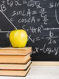 School desk in classroom, with books on background of chalk board with written formulas. Soncept Teacher`s Day. School desk in the classroom, with books on royalty free stock photos