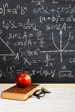 School desk in classroom, with books on background of chalk board with written formulas. Soncept Teacher`s Day. School desk in the classroom, with books on royalty free stock image
