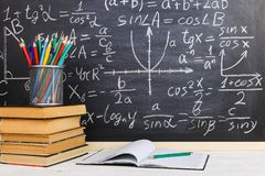 School desk in classroom, with books on background of chalk board with written formulas. Soncept Teacher`s Day. School desk in the classroom, with books on stock photo