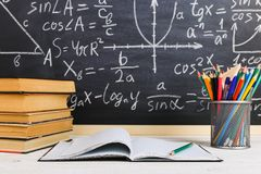 School desk in classroom, with books on background of chalk board with written formulas. Soncept Teacher`s Day. School desk in the classroom, with books on stock image