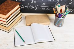 School desk in classroom, with books on background of chalk board with written formulas. Soncept Teacher`s Day. School desk in the classroom, with books on royalty free stock photo