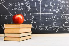 School desk in classroom, with books on background of chalk board with written formulas. Soncept Teacher`s Day stock images