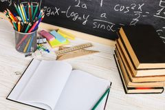 School desk in classroom, with books on background of chalk board with written formulas. Soncept Teacher`s Day stock photos