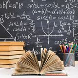School desk in classroom, with books on background of chalk board with written formulas. Soncept Teacher`s Day royalty free stock photo