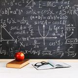 School desk in classroom, with books on background of chalk board with written formulas. Soncept Teacher`s Day stock image