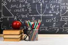 School desk in classroom, with books on background of chalk board with written formulas. Soncept Teacher`s Day stock photo