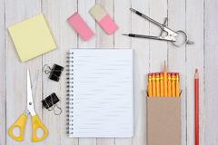 School Desk Items. A group of items typically found in a school desk. Items include: erasers, pencils, compass, scissors, paper, note pad, paper clips, shot from Stock Photos