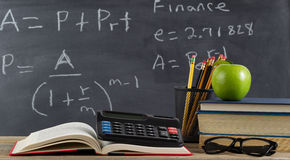 School desktop for learning finance formulas. Student desk, for finance course, in front of chalkboard with financial formulas stock photography