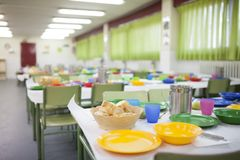 School dining room. Tables prepared for children to eat with glasses, plates, jugs stock photo