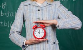 School discipline concept. Schedule and regime. Alarm clock in female hands close up. Teachers attributes. Alarm clock. In hands of teacher or educator royalty free stock photos